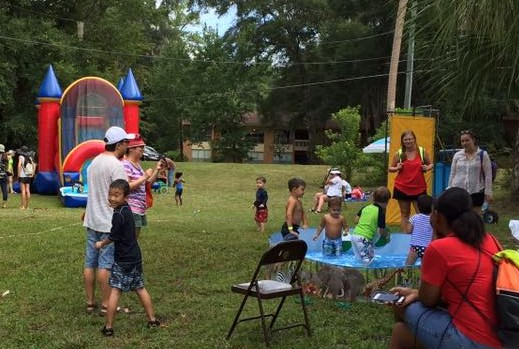 children and adults playing in kiddie pool and bounce house