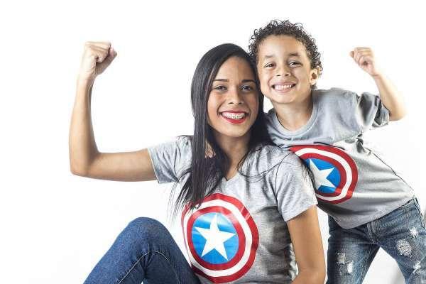 woman and child both wearing gray t-shirt with Captain America shields on them and hold up their arms flexing their muscles