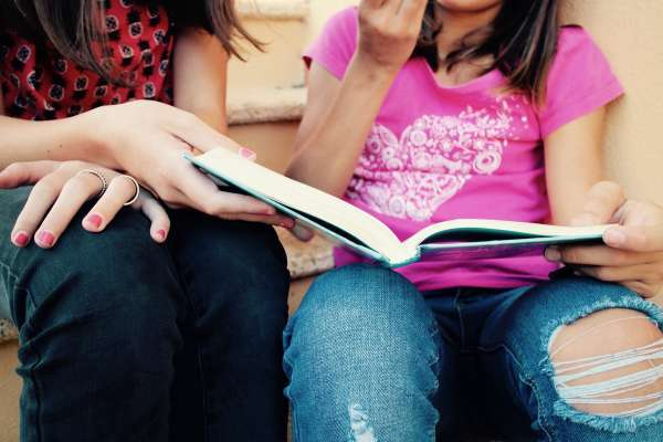 woman and girl holding a book