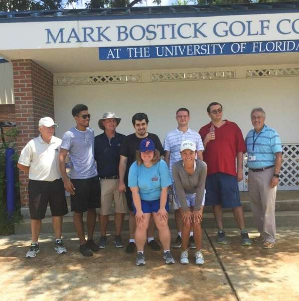 Several People posing in front of a building that has a sign that reads Mark Bostick Golf Course at the University of Florida
