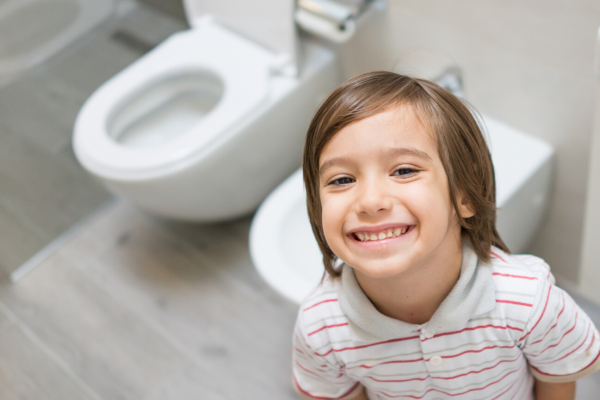 smmiling young child standing in front of a toilet