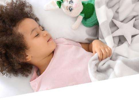 young girl sleeping in bed with blanket and toy