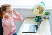 Young girl with glasses smiling while looking at laptop